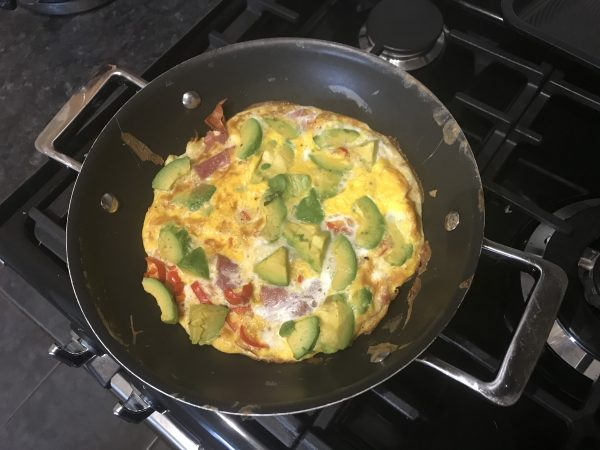 Salami and avocado frittata in a pan